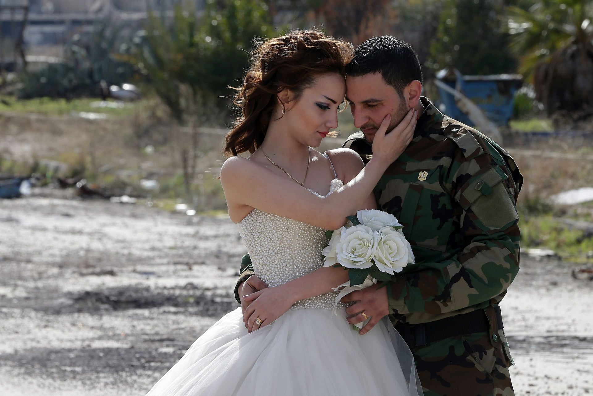 Uniform-clad groom Hassan Youssef and bride Nada Merhi strike a pose in Homs, Syria, on February 5, 2016.