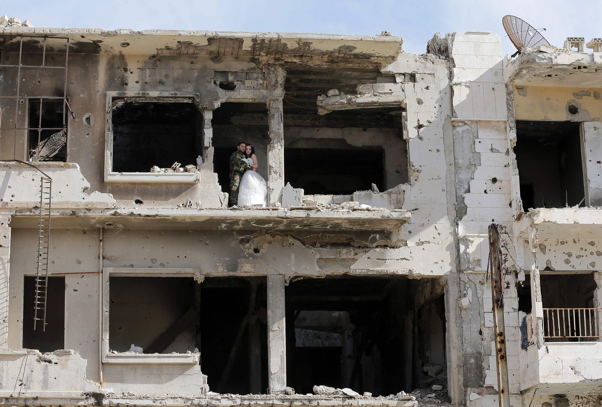 A shelled building in Homs, Syria, serves as the surprising setting for Nada Merhi and Hassan Youssef's wedding photos on February 5, 2016.