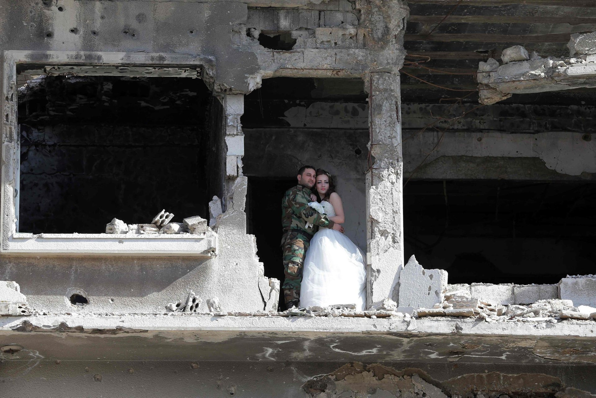 Nada Merhi and Hassan Youssef look out at the war-torn Syrian city of Homs as they pose for their wedding photos on February 5, 2016.