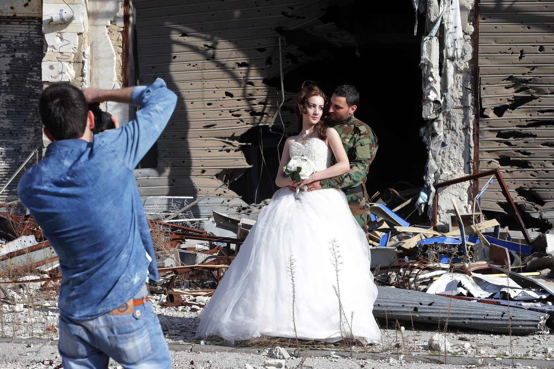 A photographer shoots couple Nada Merhi and Hassan Youssef against an unusual background in Homs, Syria, on February 5, 2016.