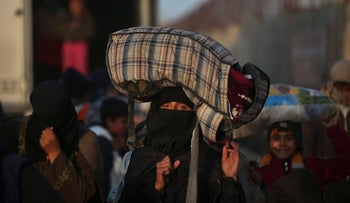 Syrians carry belongings as they arrive at the Bab al-Salameh border crossing with Turkey, in Syria, Saturday, Feb. 6, 2016.