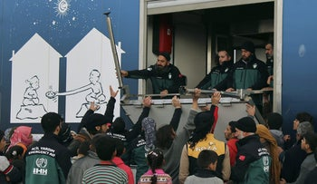 Syrians gather to collect food from the group workers at An IHH refugee camp, a temporary refugee camp for displaced Syrians in northern Syria, near Bab al-Salameh border crossing with Turkey, Sunday, Feb. 7, 2016.