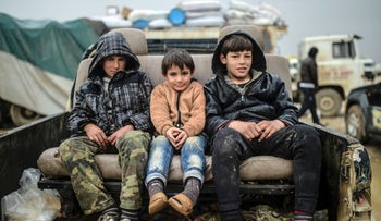 Children sit on a car as Syrians fleeing the northern embattled city of Aleppo wait on February 6, 2016 in Bab-Al Salam, near the city of Azaz, northern Syria, near the Turkish border crossing.