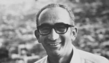 Photograph of Max Yasgur at the Woodstock festival in 1969, wearing glasses and a white shirt.