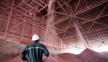 An employee watches as red potash is deposited onto storage mounds inside a warehouse at ICL Fertilizer's Dead Sea Works, part of Israel Chemicals Group, on the Dead Sea, Israel, May 6, 2013.