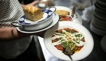 A waiter carries plates of food at Georgian restaurant Nanuchka in Tel Aviv.