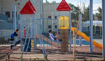 Children enjoying the new playground in Sur Baher, February 9, 2016.