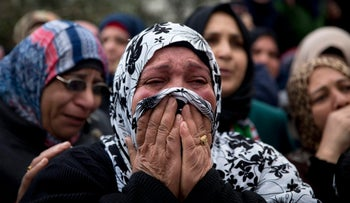 Palestinian relatives cry during a funeral held in the West Bank village of Sae'er for four Palestinians killed by Israeli military after trying to attack soldiers, January 9, 2016.