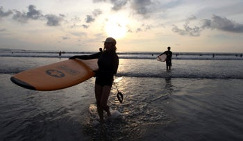Tourists carry their surfboards at sunset in Bali, Indonesia, Friday, Jan. 15, 2016.