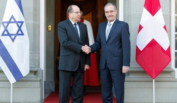 Swiss Defense Minister Guy Parmelin, right, and Israel's Defense Minister Moshe Ya'alon shaking hands during an official visit in Bern, Switzerland, February 11, 2016.