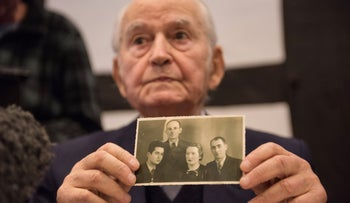 Auschwitz survivor Leon Schwarzbaum presents an old photograph showing himself next to relatives who died in Auschwitz during a press conference in Detmold, Germany, February 10, 2016.