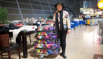 Elizabeth (Elisheva) Smit leans on a neat stack of colorful suitcases at Ben-Gurion International Airport.