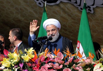 Iranian President Hassan Rohani waves during a rally in Tehran to mark the 37th anniversary of the Islamic revolution, February 11, 2016.
