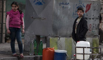 Syrian children fill plastic containers with water in the northern embattled Syrian city of Aleppo on February 9, 2016.