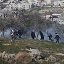 Palestinian protesters run for cover from tear gas fired by Israeli forces during clashes near Betunia after a demonstration, February 12, 2016.