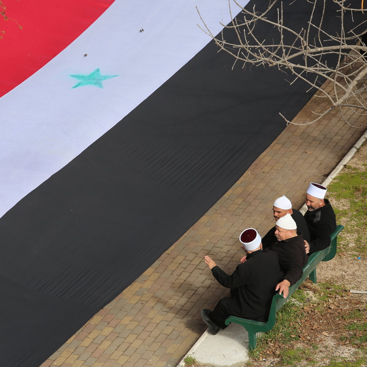 Israeli Druze sit next to a Syrian flag in the village of Buq'ata, February 14, 2016.