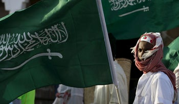 A Saudi man waves his country's flag during Janadriyah Culture Festival on the outskirts of Riyadh, Saudi Arabia February 8, 2016.