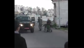 Screenshot from a video showing a Border Police officer pushing a disabled Palestinian to the ground in Hebron.