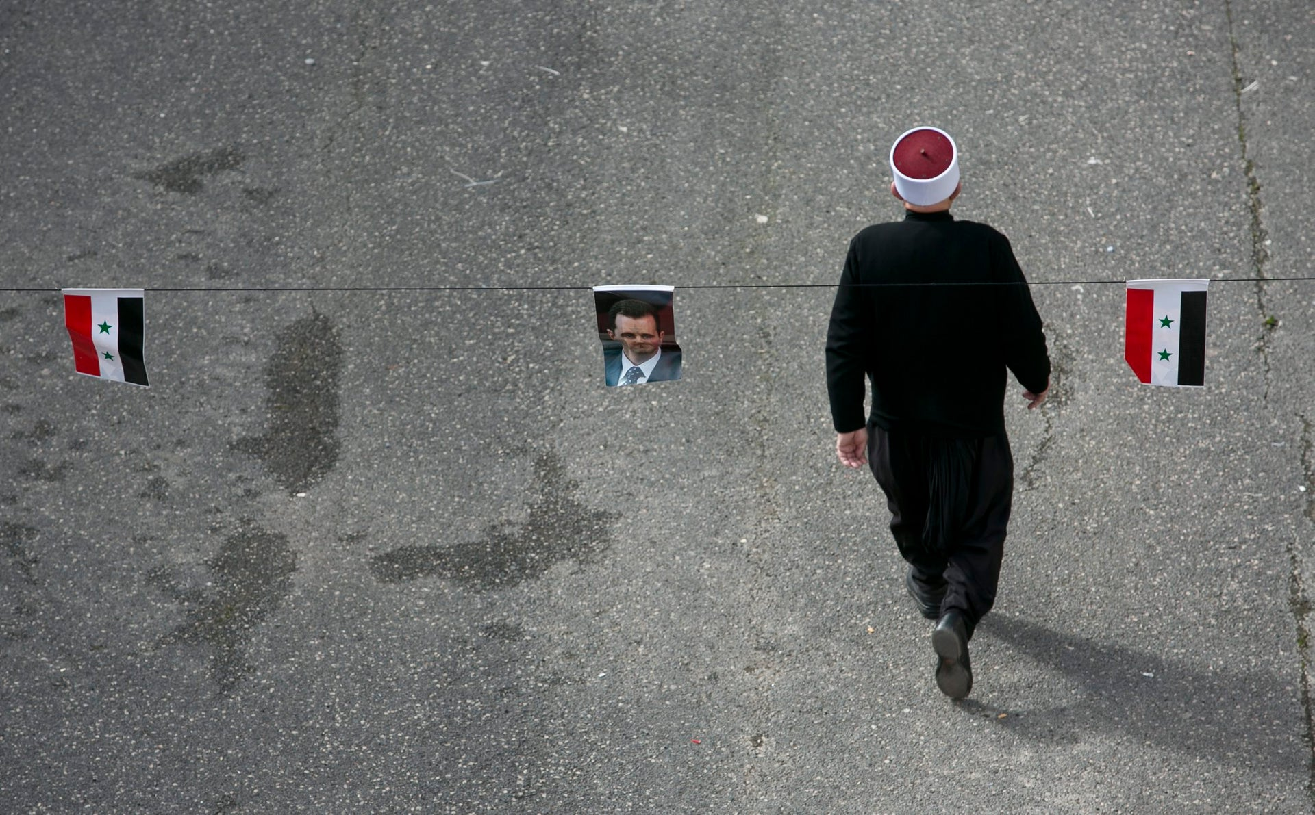 An Israeli Druze walks past Syrian flags and a picture of Bashar Assad at a protest in solidarity with the Syrian Druze community, February 14, 2016.