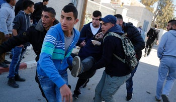 An injured Palestinian man being evacuated on February 15, 2016 at the Amari Palestinian refugee camp, near Ramallah, during clashes with Israeli soldiers that erupted after they entered the camp early in the morning.