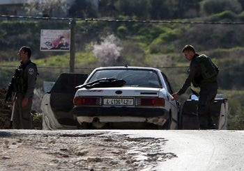 Israeli border guards inspecting a car during clashes with Palestinian demonstrators in the village of Araka, West of Jenin, February 15, 2016.