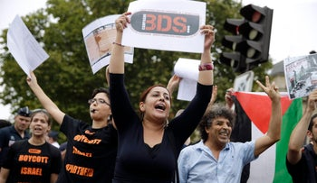 """A Pro-Palestinian protester holds a BDS placard during a gathering on the sidelines of """"Tel Aviv Sur Seine"""", on August 13, 2015."""