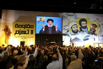 Lebanon's Hezbollah leader Hassan Nasrallah addresses his supporters through a giant screen during a rally commemorating the annual Hezbollah Martyrs' Leader Day in Beirut, Lebanon, Feb. 16, 2016.