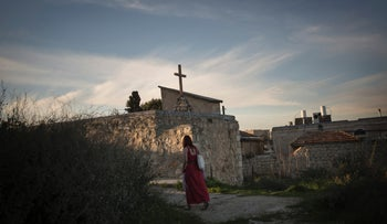 A woman walks past Greek Orthodox Church in Abu Tor, which owns the land which has been leased for development of a hotel and luxury apartments. February 17, 2016.