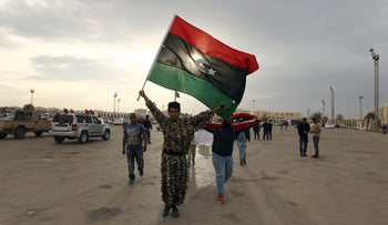 Libyans wave their flag during a demonstration marking the fifth anniversary of the Libyan revolution in Benghazi, February 17, 2016.