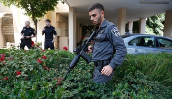Police searching outside the Tel Aviv apartment in which a 18-year-old woman was stabbed to death.