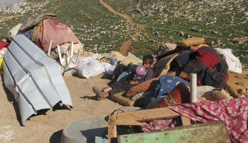 Palestinian child at Ein Rashash, this week. Israeli workers emptied the tents' contents outside before they were demolished.