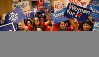 Supports of Hillary Clinton and Bernie Sanders cheer on their presidential candidates before entering a caucus site during the Nevada Democratic caucus, Saturday, Feb. 20, 2016, in Las Vegas.
