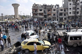 Syrians gather at the site of a double car bomb attack in the the central Syrian city of Homs on February 21, 2016.