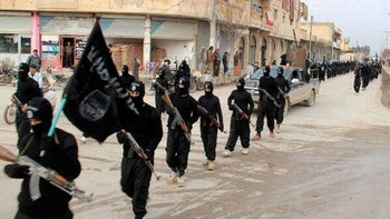 ISIS fighters marching through Raqqa, Syria.