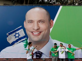 Supporters of the the Habayit Yehudi party stand in front of a campaign poster depicting the head of the party Naftali Bennett in Tel Aviv January 16, 2013.