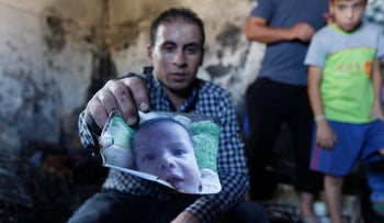 A relative holds up a photo of Ali Dawabsheh in the torched house in Duma, July 31, 2015.
