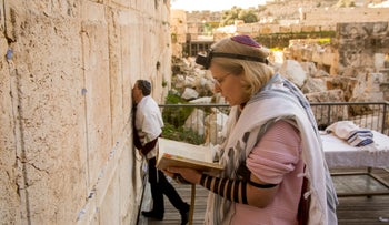 Two Reform Jews pray at the Robinson's Arch, the proposed site for an egalitarian prayer space near the main Western Wall plaza.