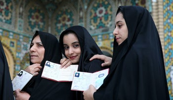 Iranian women show their identification, as they queue in a polling station to vote for the parliamentary and Experts Assembly elections in Qom, 125 kilometers (78 miles) south of the capital Tehran, Iran, Feb. 26, 2016.