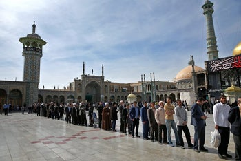 Iranians stand in line at a polling station during the parliamentary and Experts Assembly elections in Qom, 125 kilometers (78 miles) south of the capital Tehran, Iran, Friday, Feb. 26, 2016.