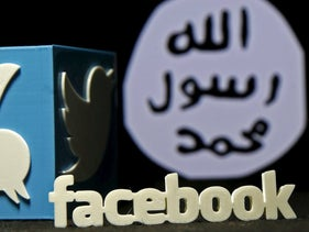 A 3D plastic representation of the Twitter and Youtube logo is seen in front of a displayed ISIS flag in this photo illustration in Zenica, Bosnia and Herzegovina, February 3, 2016.