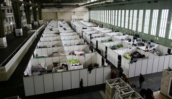 Cabins are set up inside Hanger 4 of the former airport Tempelhof to be used as a temporary emergency shelter for migrants, refugees and asylum seekers in Berlin, December 9, 2015.
