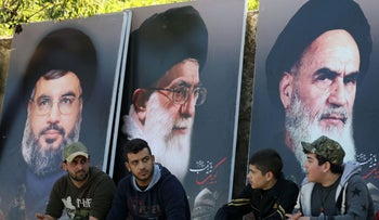 Lebanese sit in front of giant posters bearing portraits of Nasrallah, Khomeini and Khamenei, March 1, 2016.