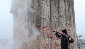 Workers removing anti-Semitic graffiti from a Holocaust memorial at a former Nazi concentration camp in Plaszow, southern Poland, on Saturday, March 13, 2010.