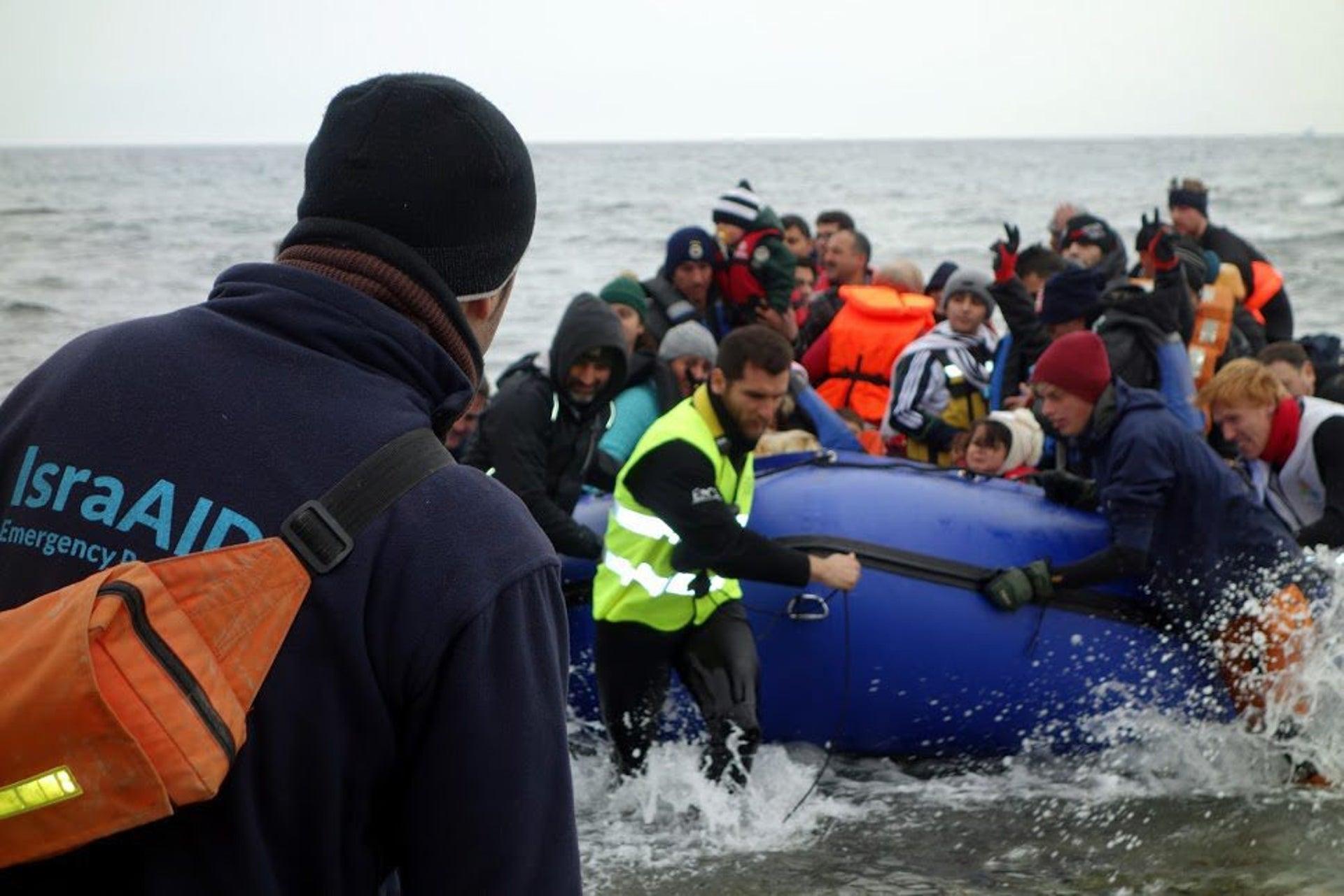 IsraAID and other volunteers receiving a boatload of refugees arriving in Lesbos, Greece.