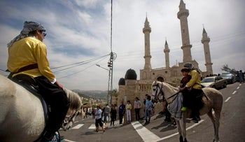 Palestinian ride their horses near a mosque in the Arab village of Abu Ghosh, on the outskirts of Jerusalem, March 23, 2014.