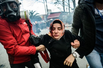 Journalists carry an injured woman after Turkish riot-police used tear gas to disperse supporters in front of the headquarters of Turkish daily newspaper Zaman in Istanbul on March 5, 2016, after Turkish authorities seized the headquarters in a midnight raid.