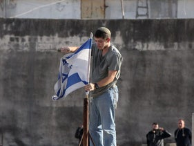 An Israeli settler fixes an Israeli flag on the roof of a building in the center of the Palestinian city Hebron, January 21, 2016.