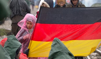 A child stands next to a Germany flag as protesting migrants stage a sit in protest on the railway tracks at the northern Greek border station of Idomeni, Wednesday, March 9, 2016.