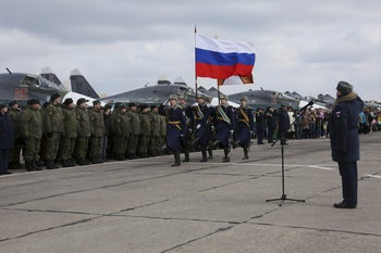 Participants attend a ceremony to welcome Russian military jets and pilots upon their return to a home airbase from Syria, in Buturlinovka in Voronezh region, Russia, March 15, 2016.