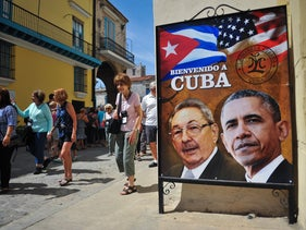 Tourists walk next to a poster of Cuban President Raul Castro and U.S. president Barack Obama ahead of Obama's landmark visit to the island, Havana, Cuba, March 18, 2016.
